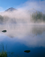 ORCAC_115 - USA, Oregon, Willamette National Forest, North (left) and Middle Sister (right) reflect in Scott Lake while early morning fog swirls above the lake.