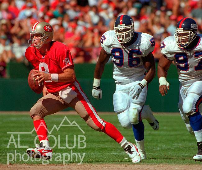 San Francisco 49ers vs. New York Giants at Candlestick Park Sunday, October 1, 1995.  49ers beat Giants 20-6.  San Francisco 49ers Quarterback Steve Young (8) pulls away from New York Giants defensive end Jamal Duff (96) and defensive tackle Robert Harris (97).