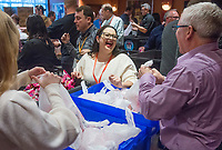 NWA Democrat-Gazette/BEN GOFF @NWABENGOFF<br /> Paulina Akel from Springdale has a laugh with Sean Madden (right) from Pittsburgh as they work with other Tyson employees to fill snack packs Wednesday, Dec. 5, 2018, at Embassy Suites Northwest Arkansas in Rogers. More than 800 Tyson employees from across the country who are in town this week attending the company's annual sales conference took the afternoon to pack and load food donations. The employees helped distribute 35,000 pounds of Tyson products to Northwest Arkansas organizations with feeding services and food banks. In addition 1,000 meal boxes, 15,000 snack packs and personal hygiene kits were packaged and distributed to Northwest Arkansas non-proffits.
