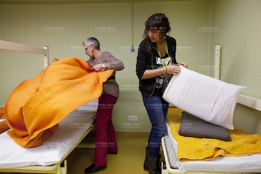 Switzerland. Geneva. Annie( left) and Nadège (right), both social workers working for the city of Geneva, are preparing beds for a late arrival of a homeless family in the fallout shelter Richemont. The bunker was constructed as civil defense measures during the Cold War and is a unit of the Civil Protection. Switzerland is unique in having enough nuclear fallout shelters to accommodate its entire population. 7.02.2014 © 2014 Didier Ruef