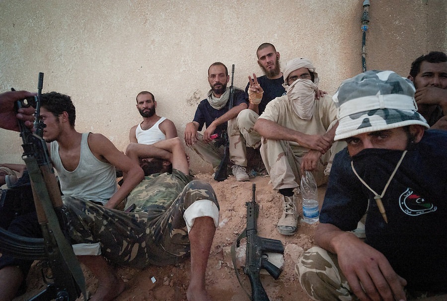Rebel fighters rest at a mosque after retreating from Gaddafi forces near Bir Ayad, Libya.