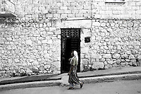Photographer: Rick Findler..05.10.12 An elderly lady walks through the town of Antakya on the border of Turkey and Syria.
