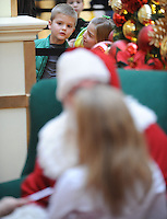 STAFF PHOTO ANDY SHUPE - Joshua Casto, 6, left, and his sister, Lauren Casto, 11, of Rogers watch Santa Claus while while waiting in line to have their photograph made with him Monday, Dec. 22, 2014, in the Northwest Arkansas Mall in Fayetteville.