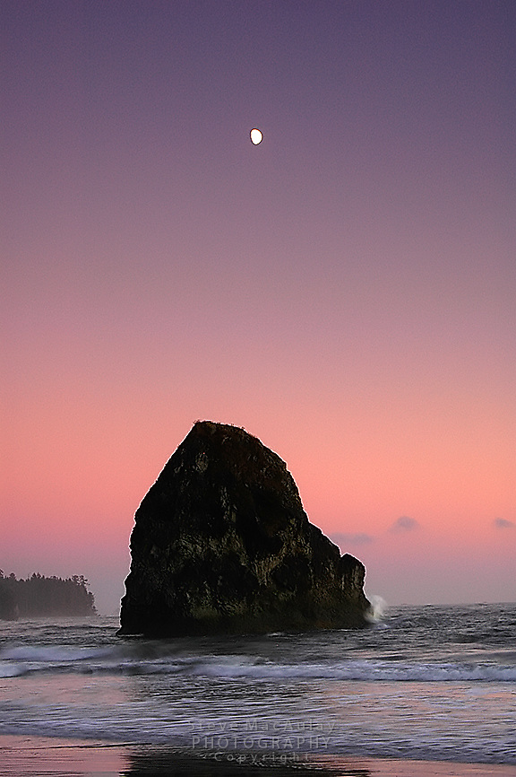 Waves crashing onto off-shore sea stack with a colorful sunset and moonrise in background, Olympic National Park, Coastal Strip, Olympic National Park, WA.