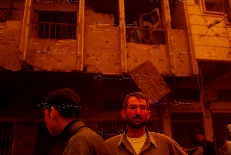 Baghdad, Iraq, March 26, 2003.Bystanders watch with disbelief the place where two US bombs fell without apparent reason in Cha'ab avenue, a busy street on the edge of Saddam City, one of the poorest neighbourhood in Baghdad.