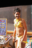 A street performer next to a jewellery stand, dancing Latin dances dressed in a very small yellow thong tanga bikini, in the restaurant El Palenque, the sword fish swordfish, in the Mercado del Puerto, the market in the port harbour harbor where many people go and eat and shop on weekends Montevideo, Uruguay, South America