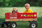 smiling toddler and puppy sitting in toy wagon at park