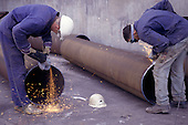 Pocerady, Czech Republic. Workers using angle grinders to clean the ends of steel pipes for welding at the power station.