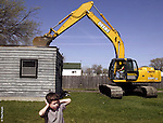 Neighborhood resident Andrew Doss, 5, tries to muffle the noise as a trackhoe digs into a house slated for destruction Thursday afternoon in Fargo. City of Fargo officials and Gate City Bank officers gathered for a news conference at the house, located at 529 20th St. N., to announce the bank's increased investment in Fargo's Neighborhood Revitalization Initiative program. The house torn down Thursday will make room for a new one to be build by Fargo North High School students.