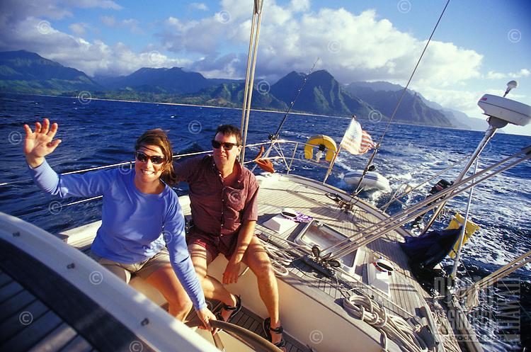 Couple sailing a 48 foot cruising yacht off the Na Pali Coast, North Shore of Kauai, Hawaii