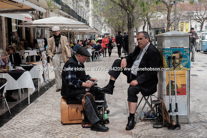 Lisbon, Portugal. 18.04.2016. Shoeshine man at work, Praca Dom Pedro V, Rossio, Lisbon. Photograph © Jane Hobson.