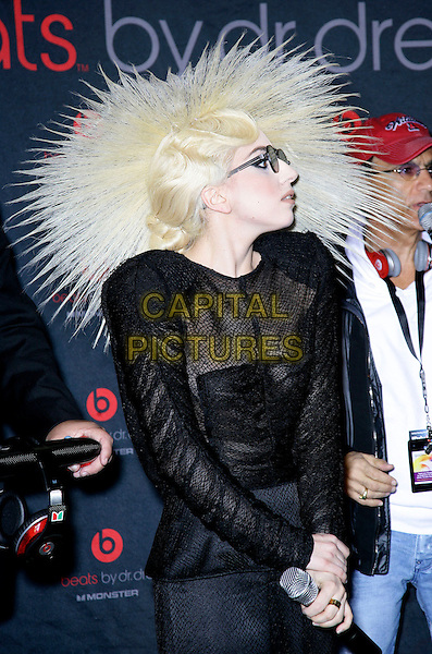 LADY GAGA (Stefani Joanne Angelina Germanotta).attends the 2010 International Consumer Electronics Show (CES), the world's largest annual consumer technology trade show held at The Las Vegas Convention Center, Las Vegas, Nevada, USA, .7th January 2010..half length wig hair sunglasses round black sheer see through thru shoulder pads knitted knit ruched top profile microphone dress hat hairspray.CAP/ADM/MJT.© MJT/AdMedia/Capital Pictures.