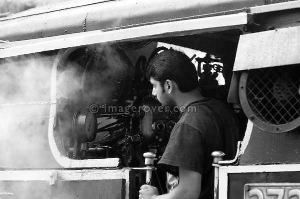 "Engine driver in the steam locomotive ""Nilgiri Queen"" of the Nilgiri Mountain Railway at Coonoor Station. India, Tamil Nadu 2005. --- Info: The Nilgiri Mountain Railway (NMR) is the only rack railway in India and connects the town of Mettupalayam with the hill station of Udagamandalam (Ooty), in the Nilgiri Hills of southern India. The construction of the 46km long meter-gauge singletrack railway in Tamil Nadu State was first proposed in 1854, but due to the difficulty of the mountainous location, the work only started in 1891 and was completed in 1908. This railway, scaling an elevation of 326m to 2,203m and still in use today, represented the latest technology of the time. In July 2005, UNESCO added the NMR as an extension to the World Heritage Site of the Darjeeling Himalayan Railway."