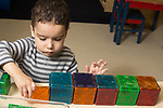 Education preschool 3-4 year olds boy building row of cubes with magnetic connecting tiles