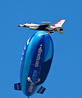 A meber of the US Air Force Thunderbirds flies past a blimp during pre-race for the Daytona 500, Daytona International Speedway, Daytona beach, Florida, February 20, 2011.  (Photo by Brian Cleary/www.bcpix.com)