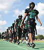 Messiah Benyehudah #35 and members of the Wyandanch varsity football team march back to their locker room before a Division IV game against Center Moriches at Wyandanch High School on Thursday, Sept. 7, 2017.