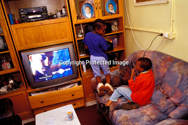 dippchi00233   Children SOWETO, SOUTH AFRICA - JULY 15: Unidentified girls playing videos in their home on July 15, 2002 in Soweto, a black township outside Johannesburg, South Africa. Soweto is the largest township in the country and itÕs estimated that about 3-4 million people resides there. Telivision, ounge, electricity, music centre (hi-fi).©Per-Anders Pettersson/ iAfrika Photos..