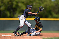 Second baseman Angelo Gumbs (21) of the New York Yankees organization takes a throw as Jeff Roy (61) slides in during a minor league spring training game against the Pittsburgh Pirates on March 22, 2014 at Pirate City in Bradenton, Florida.  (Mike Janes/Four Seam Images)