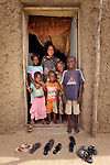 Back home in Timbuktu, Mali, after a year of living in the nation's capital, Bamako, Aissata Kantao poses with her five children in the door of their home. They fled Timbuktu after the north of Mali was seized by Islamist fighters in 2012. They returned in 2013 several months after it was liberated by French and Malian soldiers, but Kantao hasn't found work in the war-torn city.