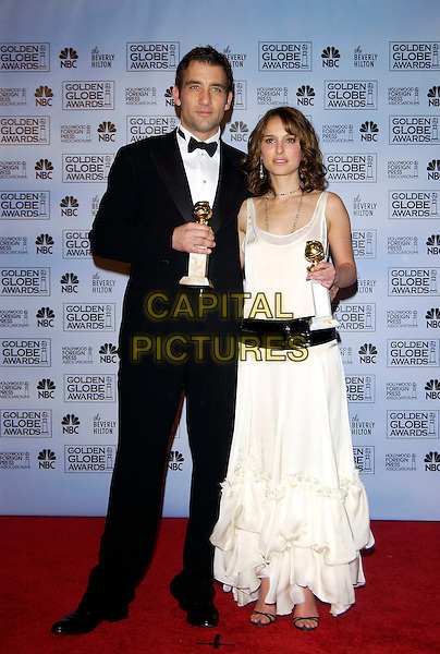 CLIVE OWEN & NATALIE PORTMAN.62nd Annual Golden Globe Awards at The Beverly Hilton Hotel Hotel, Los Angeles, California. Pressroom.January 16th, 2005 .full length, award trophy, tuxedo, white dress, profile, wide black belt ruffles layers.www.capitalpictures.com.sales@capitalpictures.com.©Capital Pictures