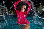 Young Latino woman swimming in a pool at night by herself