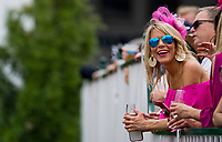 LOUISVILLE, KY - MAY 04: A woman dressed in her pink finery leans over the fence to see the race on Kentucky Oaks Day at Churchill Downs on May 4, 2018 in Louisville, Kentucky. (Photo by Eric Patterson/Eclipse Sportswire/Getty Images)