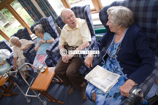 A group of older people resting in the communal lounge of a residential nursing home,