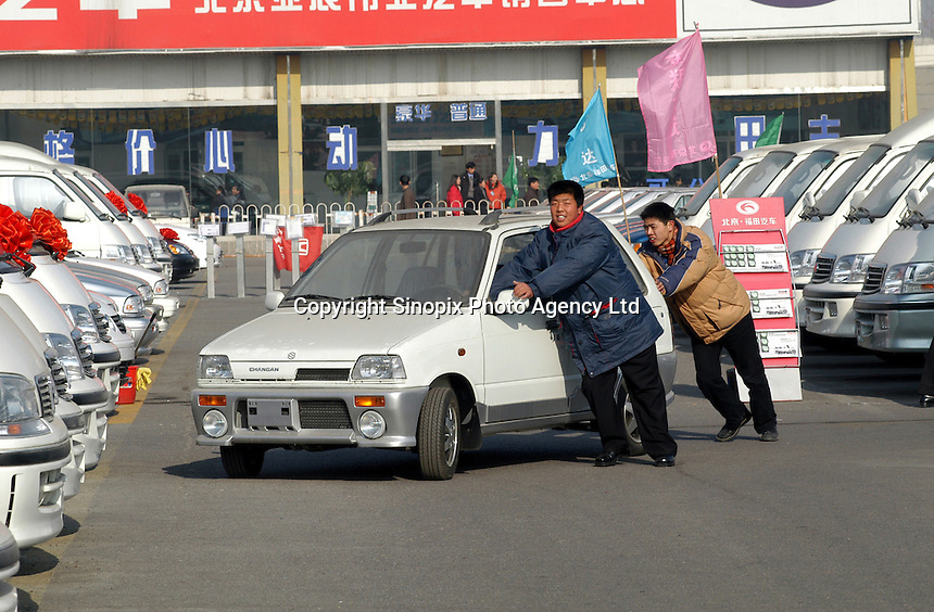Two Susiki salesmen displace a car in a car market in Beijing, China. Chinese consumers have been buying more cars as prices have fallen following the country's entry into the World Trade Organization..