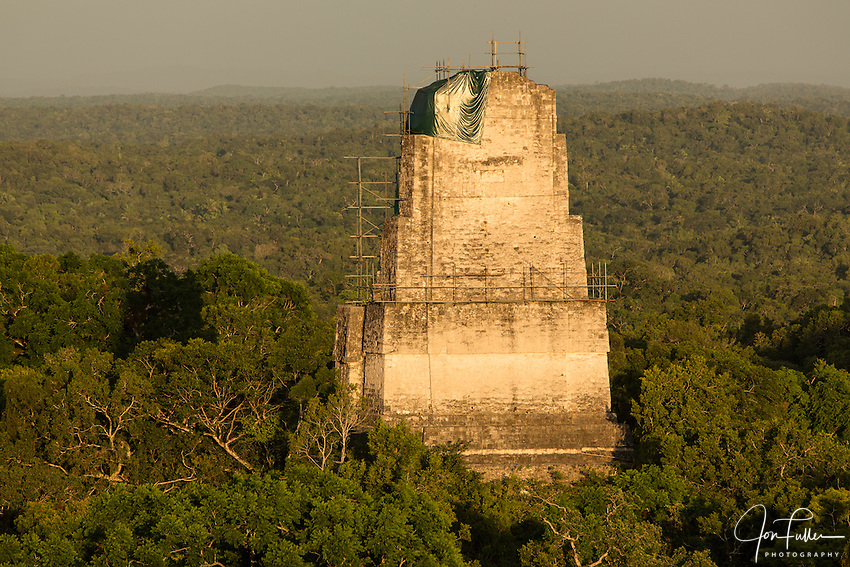 View at sunset of Temple III Temple IV in the Mayan archeological site of Tikal National Park, Guatemala.  Scaffolding for stabilization work surrounds the roof comb. A UNESCO World Heritage site since 1979.