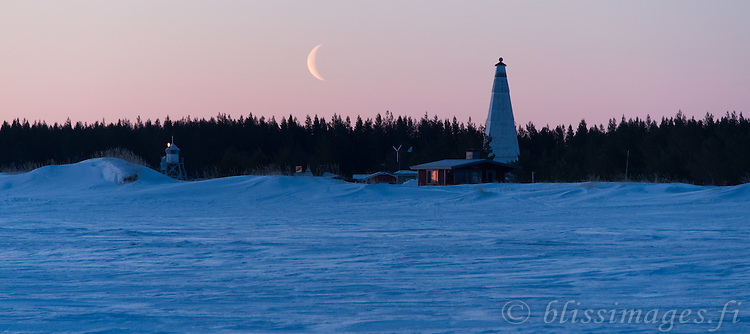 A crescent moon nestles between Keskiniemi Lighthouse and Daybeacon on the northern shore of Hailuoto Island, Finlabnd. the old and newer navigational marks are located in the Gulf off Bothnia off Oulu, Finland. Photo taken at first light in early April.