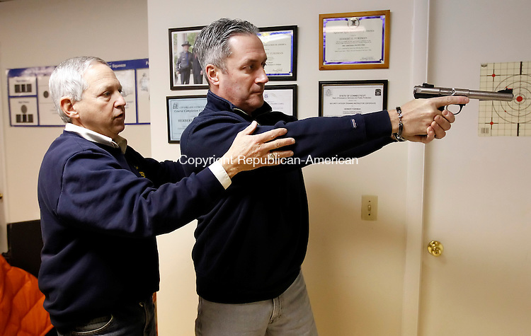 New Milford, CT- 24 January 2013-012413CM05-  Herbert G. Furham, left, a certified firearms instructor teaches Michael Grady of Brookfield, how to properly hold a firearm during a pistol permit class Thursday afternoon in New Milford.   Christopher Massa Republican-American