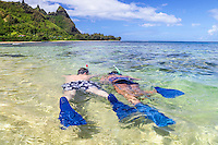 Snorkelers swim closer to the reef in the shallow waters at Tunnels Beach on Kaua'i.