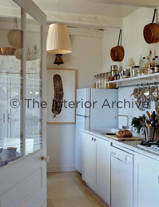 White-painted contemporary units have resulted in a cool and uncluttered yet rustic feel to this kitchen