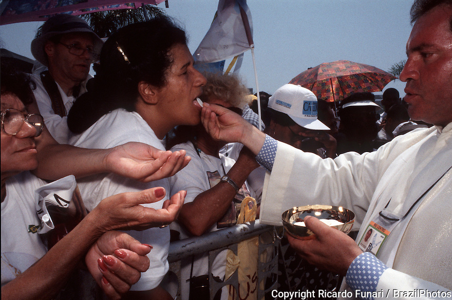 Religion in Latin America, Brazil. Outdoor mass, clerical. Catholicism. Women receives the Holy communion from priest. Religious fervour, faith.