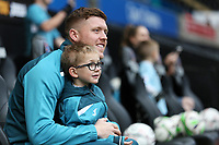 Alfie Mawson of Swansea City embraces a young boy as he arrives prior to the game during the Premier League match between Swansea City and Crystal Palace at The Liberty Stadium, Swansea, Wales, UK. Saturday 23 December 2017
