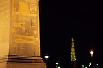Luxor Obelisk in the Concorde Plaza with view of the Eiffel Tower illuminated at night, Paris, France.