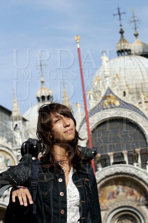 Una turista gioca con i piccioni di fronte alla Basilica di San Marco a Venezia.<br /> A tourist plays with pigeons in front of the Patriarchal Cathedral Basilica of St. Mark in Venice.<br /> UPDATE IMAGES PRESS/Riccardo De Luca