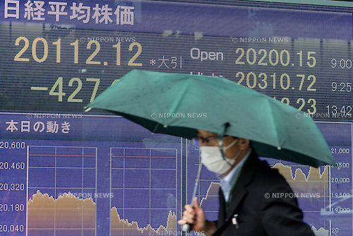 A pedestrian walks past an electronic stock board showing Japan's Nikkei Stock Average, which dropped 427.67 or 2.08% on Monday, July 6, 2015. After Greece voted against accepting further EU imposed austerity measures in a national referendum on Sunday the Nikkei Index fell 427.67 points to 20112.12 on its first journey of the week. (Photo by Rodrigo Reyes Marin/AFLO)