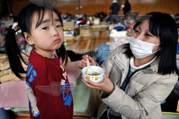 A woman feeds her daughter cereal in a shelter for people displaced from the town of Namie that has been set up in nearby Dakeshita. Namie is the closest town to the Fukushima nuclear plant.  On 11 March 2011 a magnitude 9 earthquake struck 130 km off the coast of Northern Japan causing a massive Tsunami that swept across the coast of Northern Honshu. The earthquake and Tsunami caused extensive damage and loss of life and the damage caused to the Fukushima nuclear plant has created an ongoing nuclear crisis.