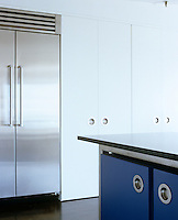 The flat doors and the drawer fronts of the cupboards and units in this contemporary kitchen are simply painted in blue and white and feature recessed porthole-style handles
