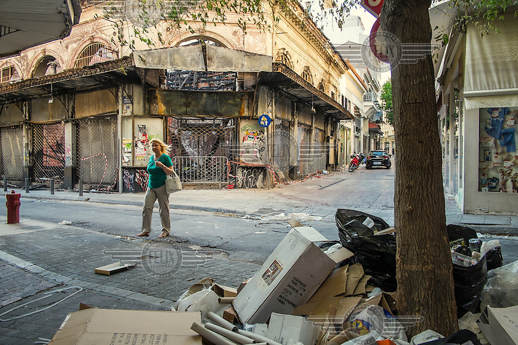 ATHENS, GREECE: garbage accumulates in fornt of the remains of a shop burnt by protesters in March 2011.