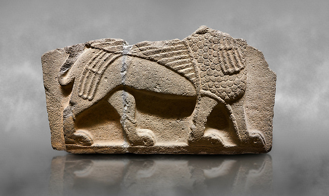 Hittite monumental relief sculpted orthostat stone panel from Water Gate Basalt, Karkamıs, (Kargamıs), Carchemish (Karkemish), 900-700 B.C. Anatolian Civilisations Museum, Ankara, Turkey.<br /> <br />  A portion of the body and the feet of the Sphinx. Its chest was processed as fish flakes. Parallel lines on its wings draw attention.  <br /> <br /> On a grey art background.