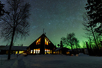 Night time winter photo of main lodge at Winter Lake Lodge with stars and faint Aurora Borealis (Northern Lights). Southcentral, Alaska.