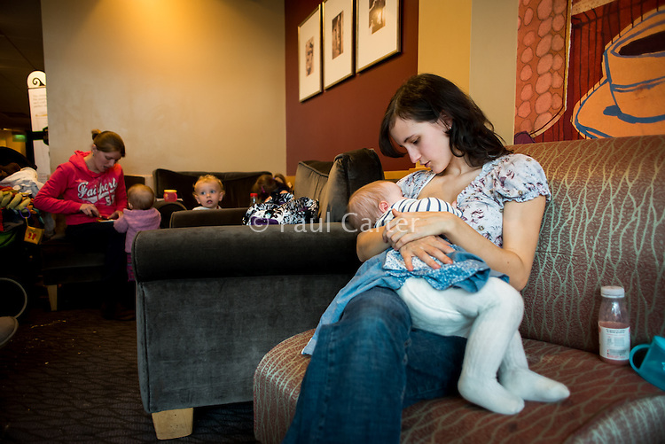 A young woman breastfeeding her ten month old baby in a coffee shop.<br /> <br /> Image from the &quot;We Do It In Public&quot; documentary photography project collection: <br />  www.breastfeedinginpublic.co.uk<br /> <br /> Dorset, England, UK<br /> 17/04/2013