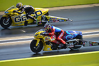 Sept. 22, 2012; Ennis, TX, USA: NHRA pro stock motorcycle rider Scotty Pollacheck (near) races alongside Karen Stoffer during qualifying for the Fall Nationals at the Texas Motorplex. Mandatory Credit: Mark J. Rebilas-US PRESSWIRE