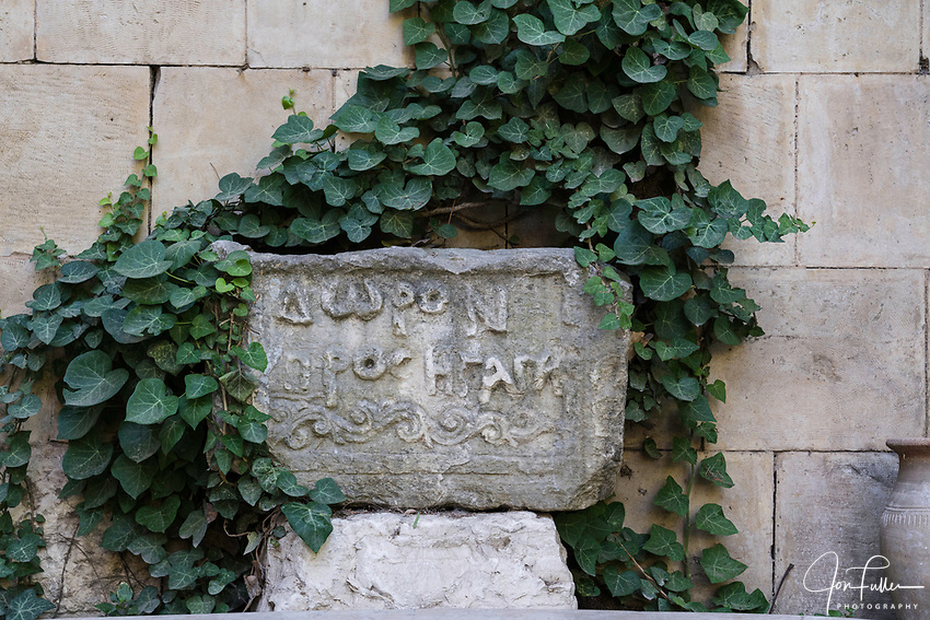 A ancient carved stone of early Byzantine uncial script in the garden of the Church of Saint Anne in Jerusalem.  The Church was built on the site of an earlier Byzantine basilica.  The Old City of Jerusalem and its Walls is a UNESCO World Heritage Site.  Uncial script was commonly used from the 4th to 8th Centuries A.D. by Latin and Greek scribes.