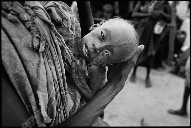 A mother holds her son as he hovers between life and death in a refugee camp. More than 350,000 Somalis died between 1991 and the end of 1992, as a result of the famine and related illnesses created by the civil war. Baardheere, Somalia, November 1992