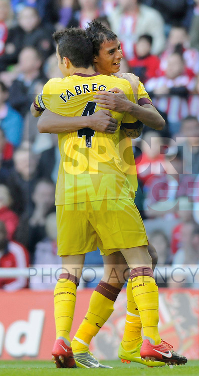 Arsenal's first goalscorer Cesc Fabregas celebrates with Marouane Chamakh.