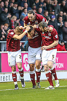 Rod McDonald of Northampton Town (centre) celebrates scoring his team's third goal against Morecambe as John-Joe O'Toole of Northampton Town jumps on his back during the Sky Bet League 2 match between Northampton Town and Morecambe at Sixfields Stadium, Northampton, England on 23 January 2016. Photo by David Horn / PRiME Media Images.