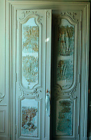 Tall blue carved wooden doors are decorated with a distressed silk collage of gold calligraphy.
